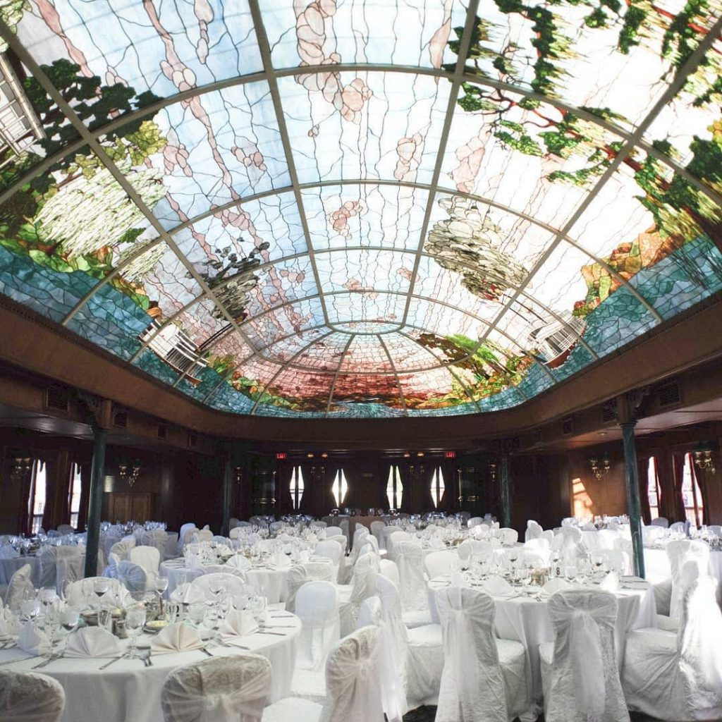 reception setup with white chairs and tables under stained glass ceiling at bahia resort hotel in san diego