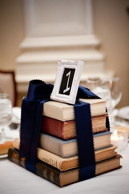 stacks of books wrapped in ribbon as a wedding reception centerpiece