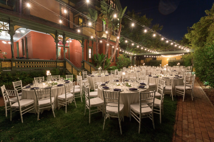 reception setup with white tablecloth tables under twinkle lights at night at britt scribbs manor in san diego