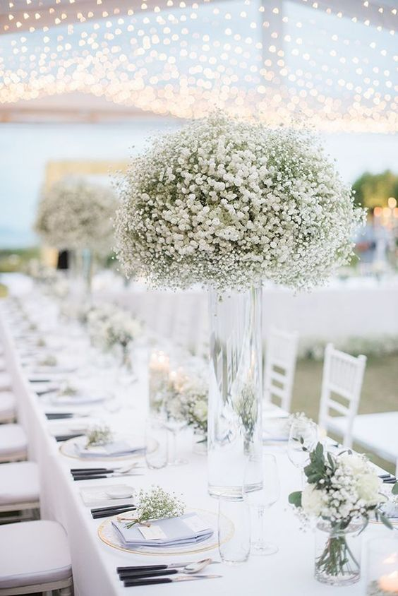 white flowers in a clear tall vase at a wedding reception table