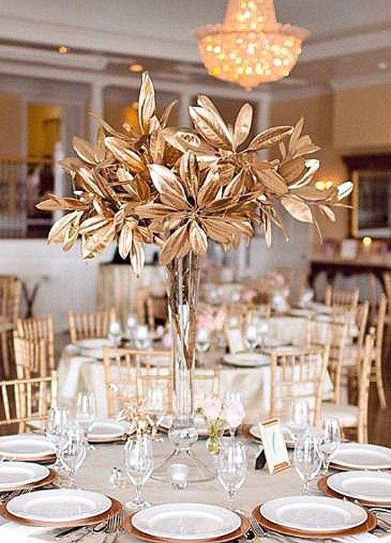 tall, gilded flower centerpieces arranged on wedding reception table