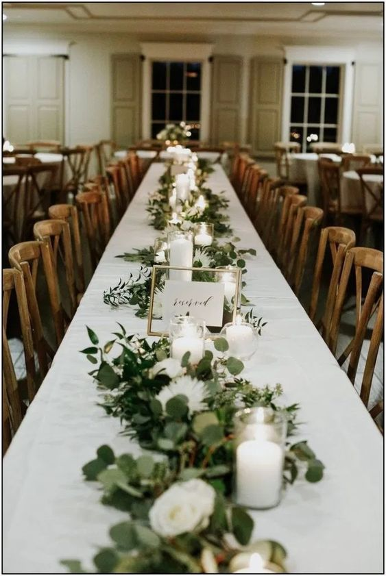 garlands of greenery centerpiece arranged on a wedding reception table