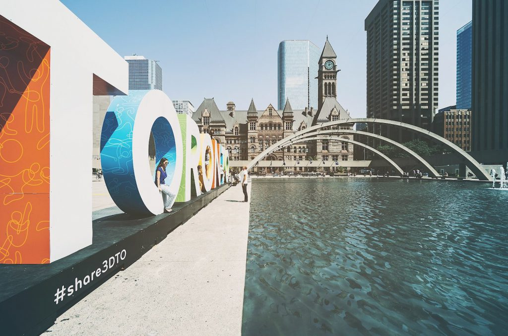 view of nathan phillips square in toronto featuring water, arches, a large toronto sign, and buildings in the background