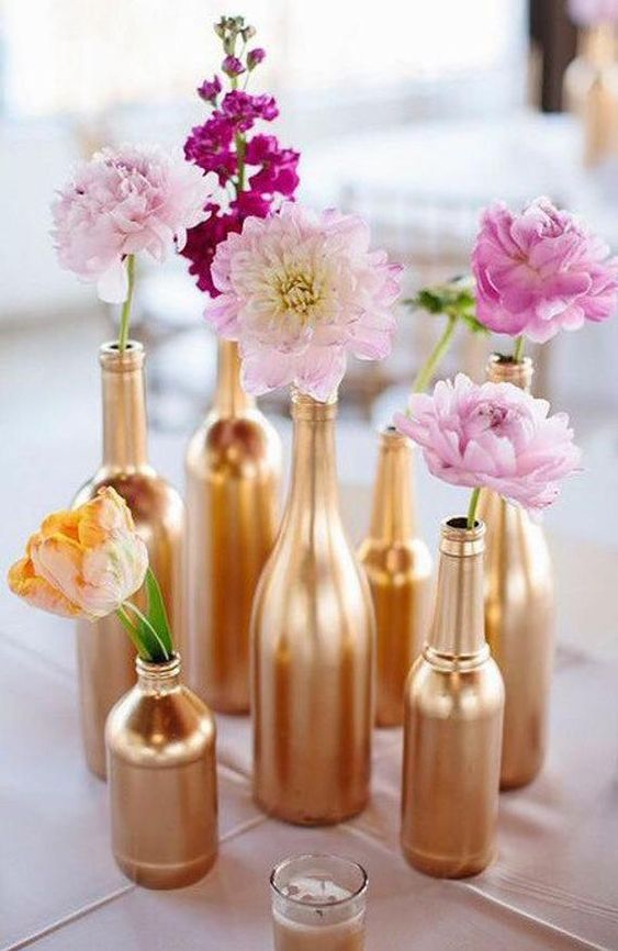 painted gold bottles filled with pink flowers on a table