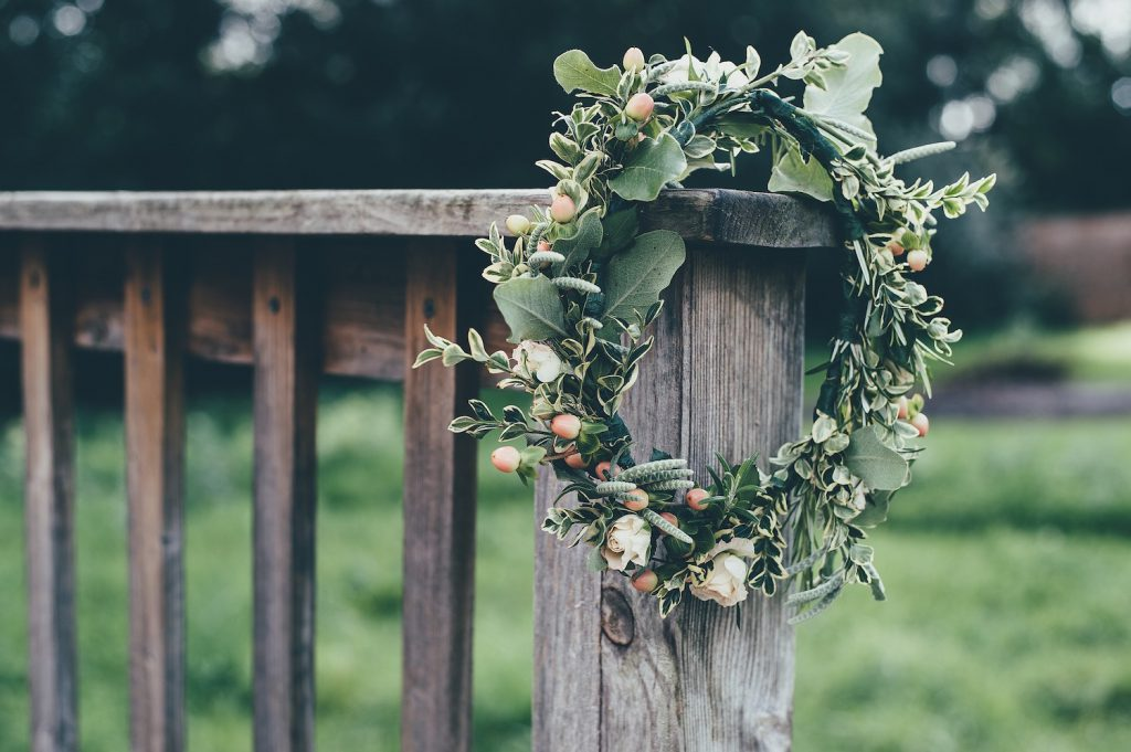 faux flower crown with greenery hanging off wooden post