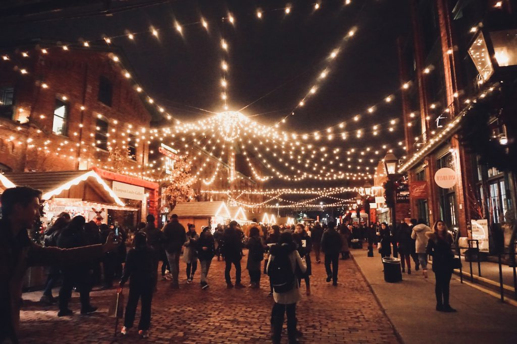 people gather at night under festive twinkle lights at the toronto christmas market