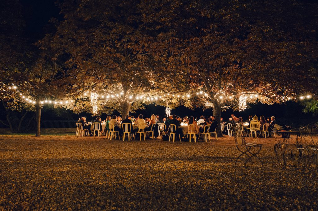 people gathered at outdoor wedding dinner next to lighted up trees