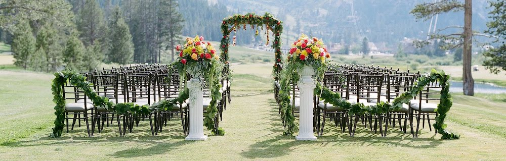 chairs, an arch, and floral displays set up for a wedding on the golf course at the resort at squaw creek