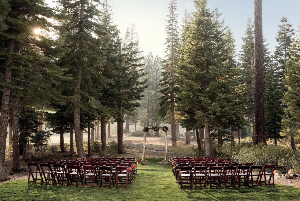 chairs and an arch for a wedding ceremony at the ritz carlton lake tahoe, set up slope-side amongst the pine trees