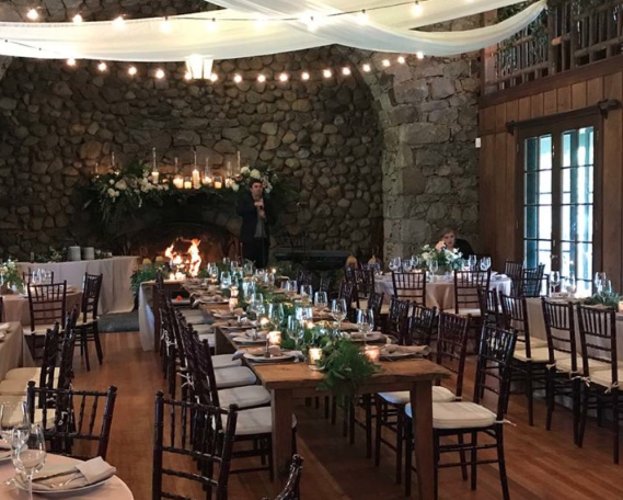 the grand hall at valhalla at lake tahoe set with tables, chairs, place settings, and centerpieces for a wedding reception