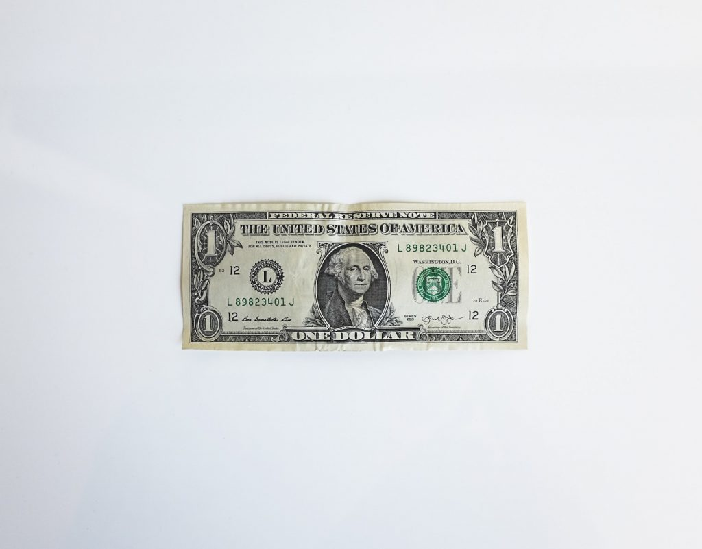 a single dollar pill lying flat on white background