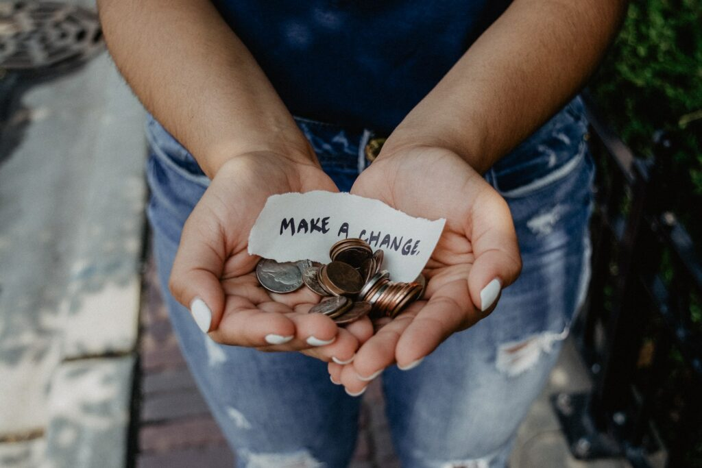 hands holding change with note that says 'make a change'