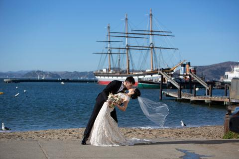 a man and woman in wedding attire kissing on a beach