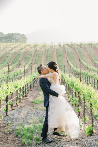 a man and woman kissing in a vineyard