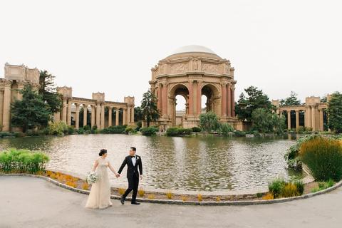 a man and woman in wedding attire walking by a pond with Palace of Fine Arts in the background