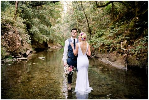 a man and woman posing for a picture next to a river