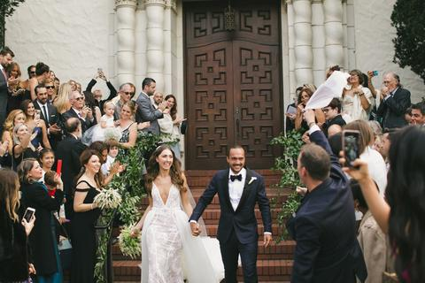 a man and woman walking down a aisle with a crowd watching