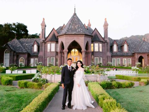 a man and woman posing in front of a mansion
