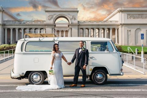 a bride and groom posing in front of a white van