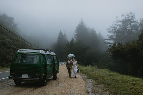 a couple standing on a road with an umbrella and a car on a foggy day